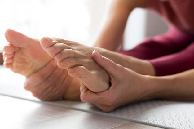Close-up de pernas e mãos fazendo exercícios de alongamento