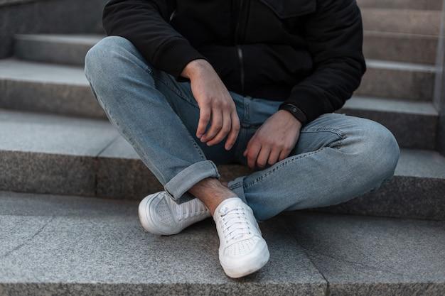 Close-up de pernas masculinas. homem com uma jaqueta preta estilosa em jeans elegantes e tênis de couro branco da moda está sentado em uma escada de pedra vintage na cidade