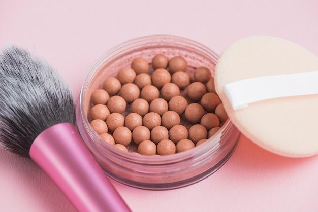 Close-up de pérolas bronzeadoras; esponja e pincel de maquiagem no fundo rosa