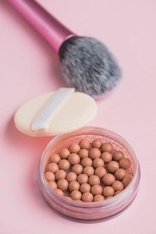 Close-up de pérolas bronzeadoras; esponja e pincel de maquiagem