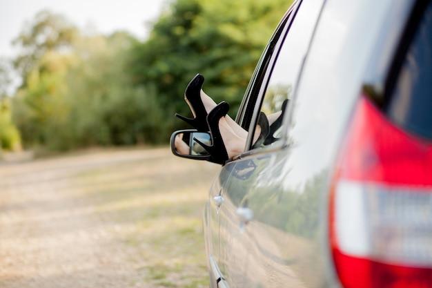 Close-up de pés com sapatos pretos de salto alto de garota atraente. ela está colocando as pernas pela janela do transporte moderno.