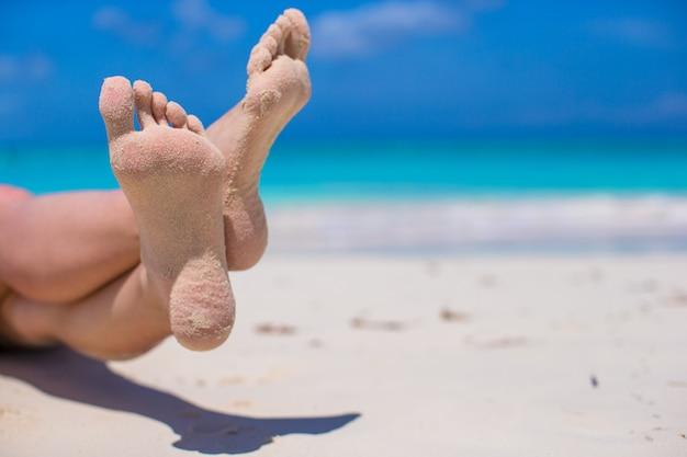 Close up de pés femininos na praia de areia branca
