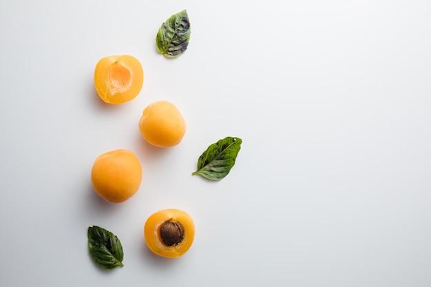 Close up de pêssegos maduros na mesa com folhas