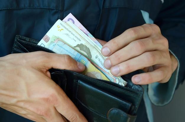 Close-up de pessoa abrindo a carteira com moeda ucraniana