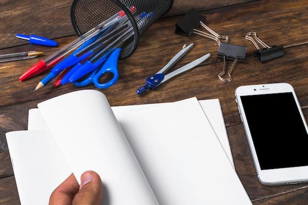 Close-up, de, pessoa, mão, girar papel branco, com, stationeries, e, cellphone