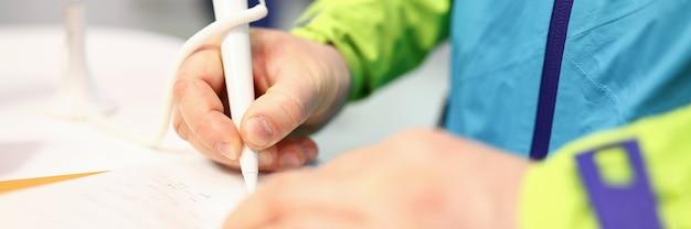 Close-up de pessoas mão assinar cheque ou recibo com caneta branca. homem de casaco brilhante. macho no banco preenchendo formulário importante no papel. conceito de dinheiro e responsabilidade