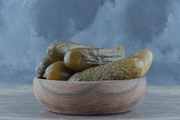 Close up de pickles caseiros em uma tigela de madeira