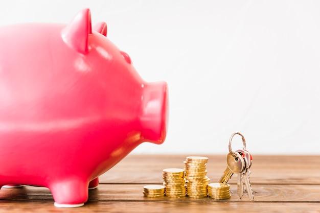 Close-up de piggybank rosa perto de moedas empilhadas e chave