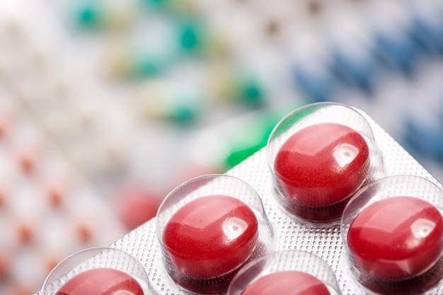 Close up de pílulas vermelhas em embalagem de plástico