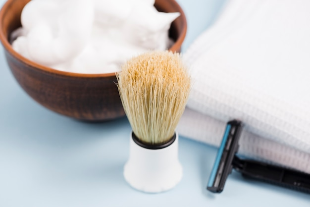 Close-up de pincel de barba clássico; espuma; navalha e guardanapo branco sobre fundo azul