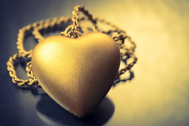 Close up de pingente de coração de ouro com colar