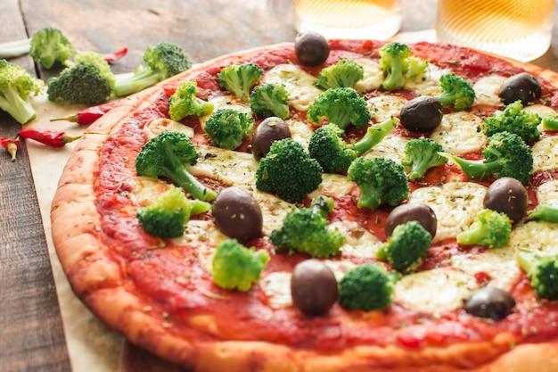 Close-up de pizza com molho de tomate; brócolis e azeitonas e queijo