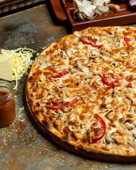 Close-up de pizza de frango com queijo e cogumelos de tomate