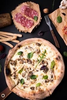 Close-up de pizza de queijo de cogumelos; fatias de calabresa; varas de pão e garfo no balcão
