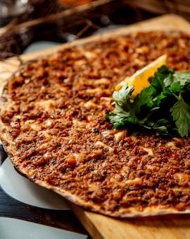 Close-up de pizza turca lahmajun com limão e salsa