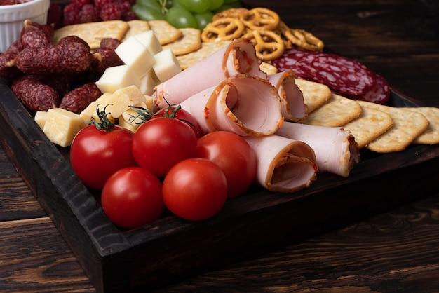 Close-up de placa de charcutaria com salsicha, fruta, biscoitos e queijo.