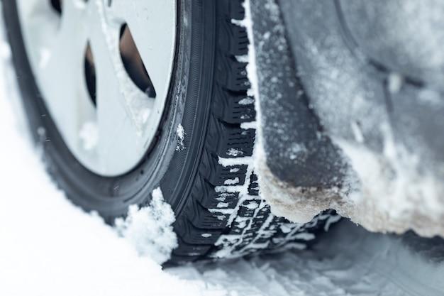 Close-up de pneus de borracha de rodas de carro na neve profunda do inverno. conceito de transporte e segurança.