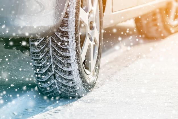 Close-up de pneus de borracha de rodas de carro na neve profunda do inverno. transporte e conceito de segurança.