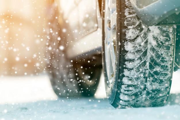 Close-up de pneus de borracha de rodas de carro na neve profunda do inverno.