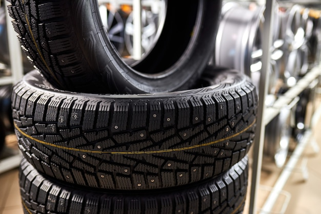 Close-up de pneus novos no centro de reparação de automóveis, pneus de inverno novos com um piso moderno isolado. foco seletivo.