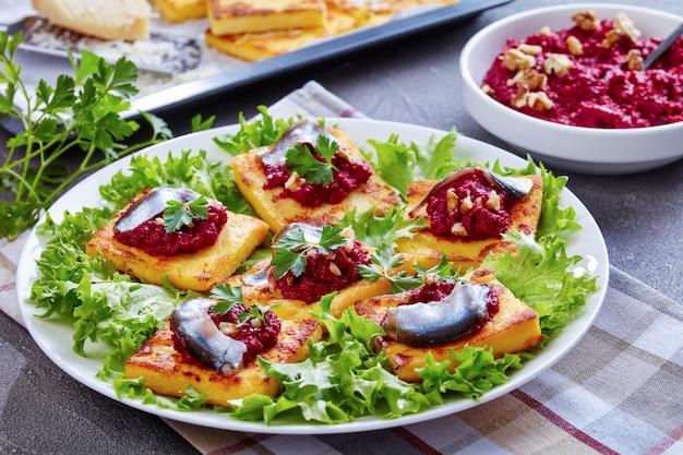 Close-up de polenta squares com purê cremoso de beterraba, coberto com anchovas e salsa em um prato branco. barras de polenta recém-assadas e parmesão em uma assadeira sobre uma mesa de concreto