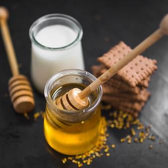 Close-up de pote de leite; pote de mel; biscoitos e pólenes de abelha em pano de fundo preto