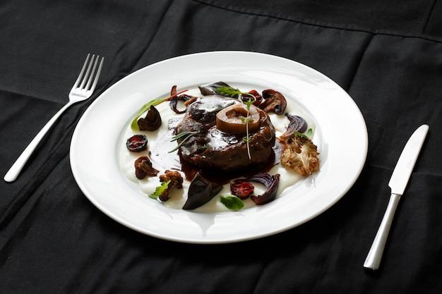 Close up de prato de carne com legumes grelhados