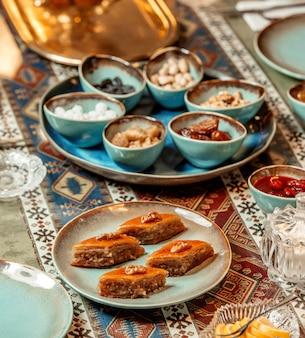 Close-up de prato pakhlava ao lado de bandeja de nozes e doces
