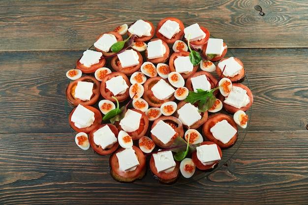 Close-up de prato redondo na mesa de madeira, servido com tomates frescos, pedaços de queijo, caviar e decorado com folhas frescas de salsa verde.