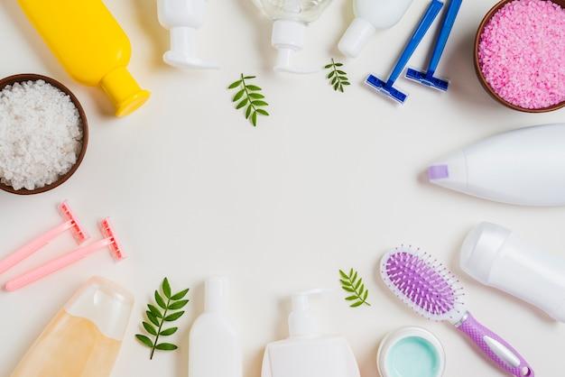 Close-up de produtos cosméticos; navalha; sal e escova de cabelo no fundo branco