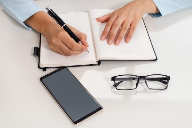 Close-up, de, professor feminino, mãos, fazendo anotações, em, workbook