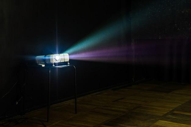 Close-up de projetor multimídia com raios de luz coloridos projetando-se na tela