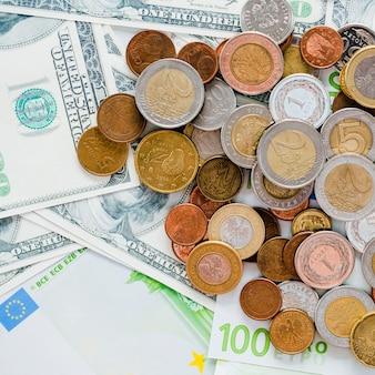 Close-up de propagação de moedas e nos notas de cem dólares