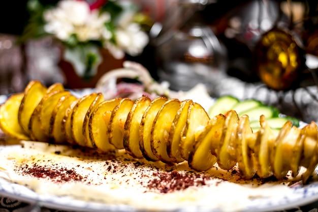 Close-up de quibe de fatias de batata no espeto de aço fino com pedaços de gordura de cordeiro