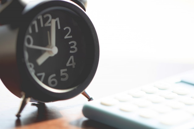 Close-up de relógio e calculadora em fundo de madeira para a hora do tex