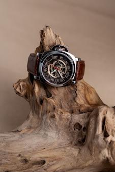 Close up de relógios de pulso de homem de luxo colocados em tronco de árvore