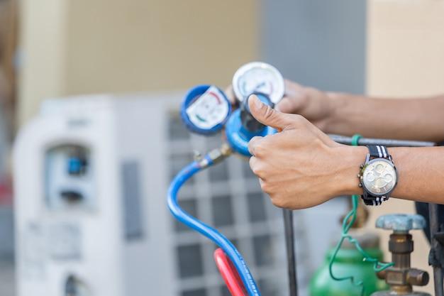 Close-up de reparação de ar condicionado, reparador no chão fixação sistema de ar condicionado