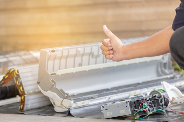 Close up de reparador desistir polegar depois de limpar o compartimento de ar condicionado