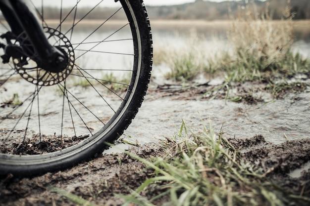 Close-up, de, roda bicicleta montanha, em, a, lama, perto, a, lago