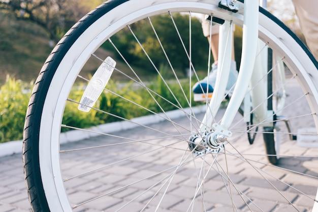 Close-up de rodas de bicicleta vintage com pneus brancos e refletor