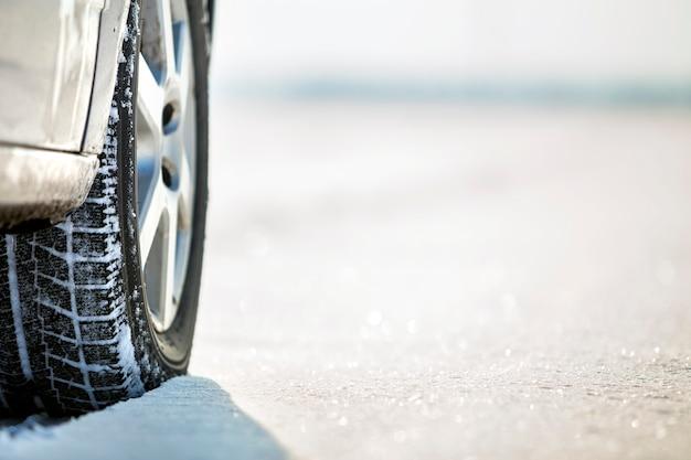 Close-up de rodas de carro pneus de borracha na estrada de neve no inverno profundo
