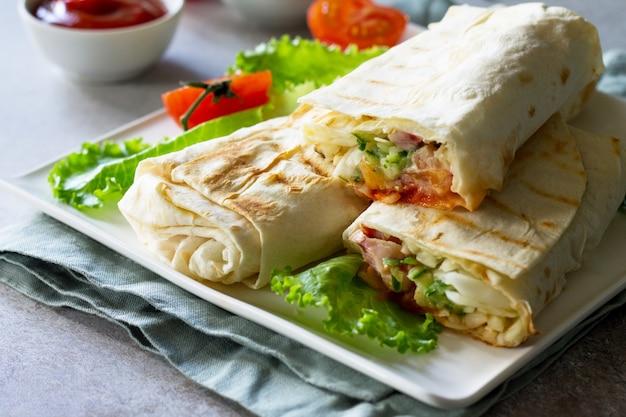 Close up de rolo de frango shawarma em uma pita com legumes frescos conceito fast food