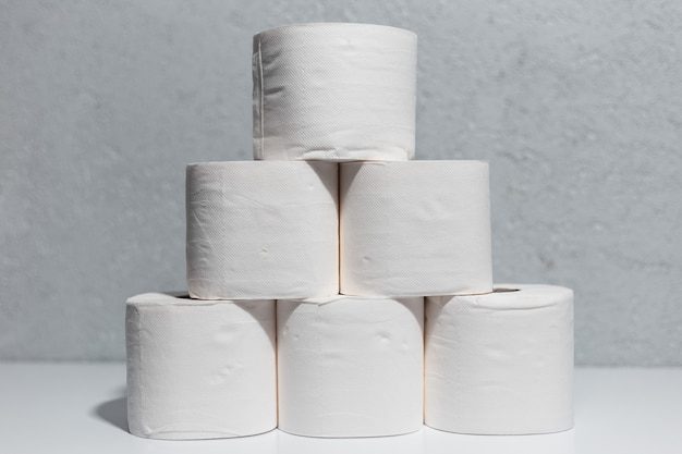 Close-up de rolos de papel higiênico na mesa branca