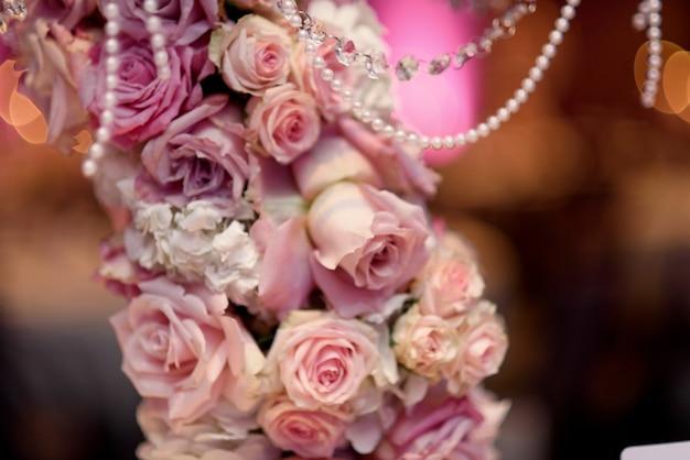 Close up de rosas rosas colocam o castiçal