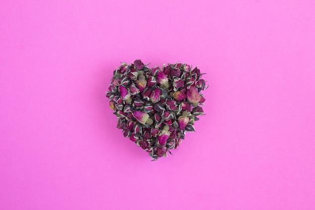Close-up de rosas secas em forma de coração no fundo rosa
