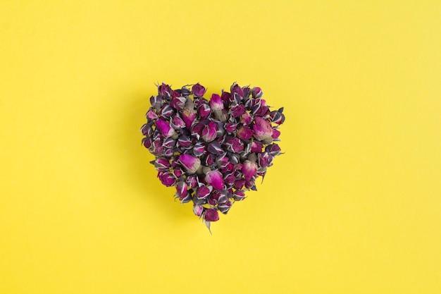 Close-up de rosas secas na forma de um coração no fundo amarelo. copie o espaço.