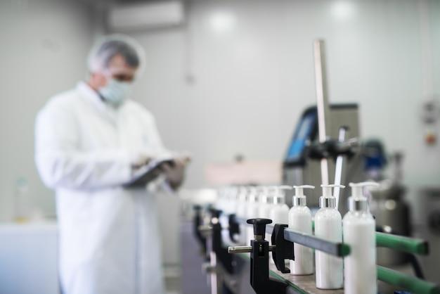 Close-up de sabonete líquido, indo em uma linha de produção na frente do trabalhador de tecidos cosméticos digitando em um tablet