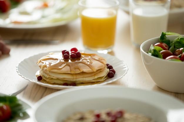 Close-up de saborosas panquecas servidas com calda e frutas