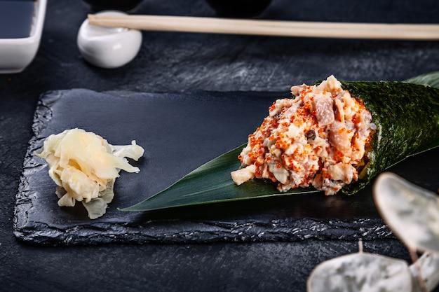 Close-up de saboroso sushi de rolo de mão com enguia e caviar de tobico servido no prato de pedra escuro com molho de soja e gengibre