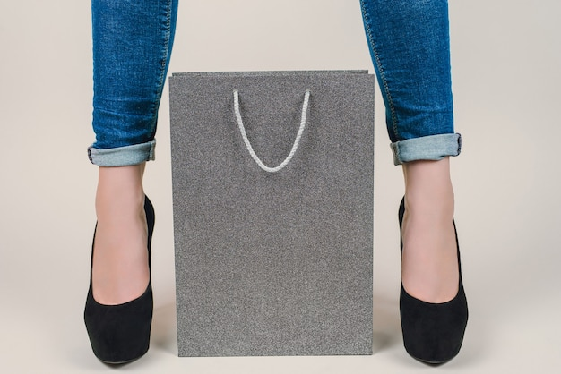 Close up de saco de papel cinza entre as pernas femininas isoladas
